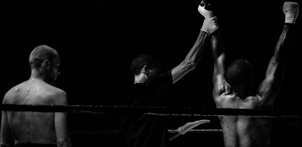 A referee raises a boxer's hands in victory.