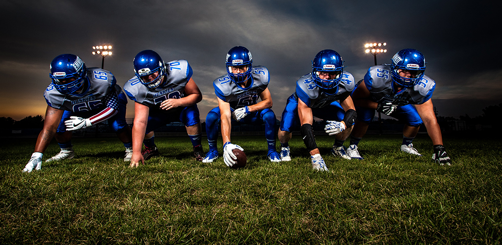 Members of a football team assemble at the line of scrimmage.