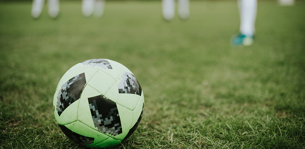 Closeup of a soccer ball on a field with players blurred in the background.