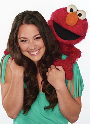As Nina on Sesame Street, Suki Lopez's job includes babysitting Elmo.