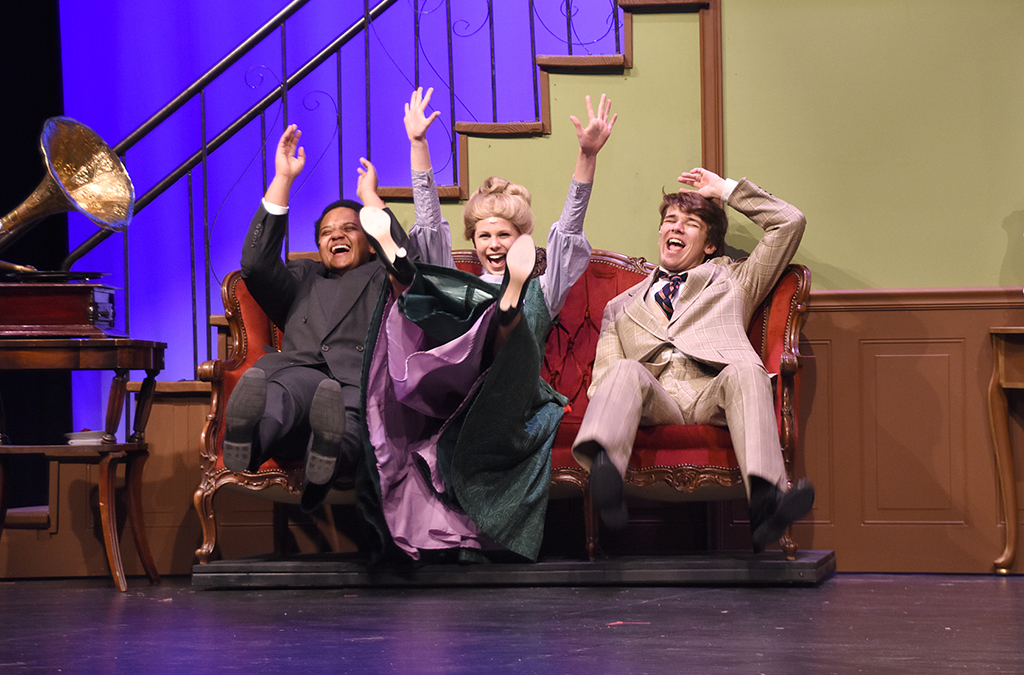 Nate Earley-Ochwada as Colonel Pickering, Shelby Brown as Eliza, and Troy Jones as Henry celebrate a breakthrough in the New Albany High School production of My Fair Lady.