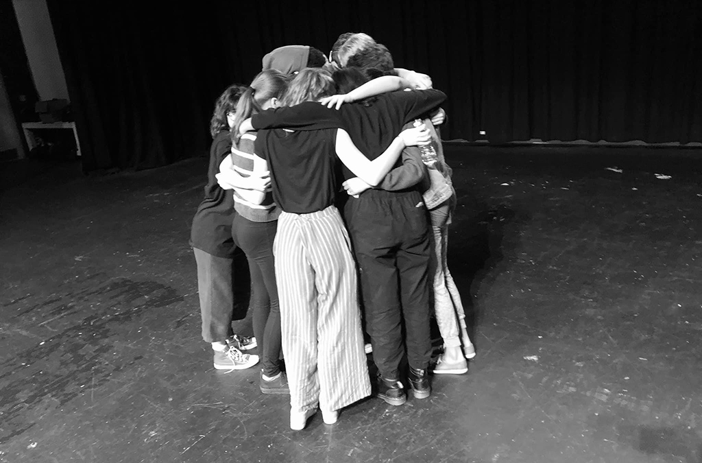 The Puffs cast celebrates closing night of the show with a group hug.