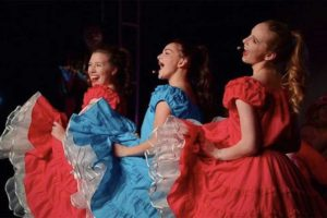 three young women dancing in bright red and bright blue dresses. they are singing