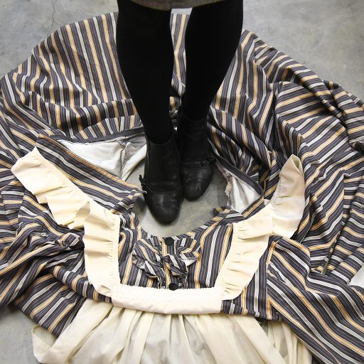 To get into a dress or skirt quickly, pool it on the floor before the show, leaving an opening wide enough to step into. During the quick change, simply step in and pull the garment up over your body. An actor can easily overhaul their costume while dressers focus on details such as shoes, wigs, gloves, etc.